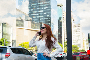Beautiful young redhead woman talking with smart phone