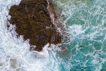 Drone aerial view of waves crashing over rocks on Lumaha'i beach on north shore of Kauai