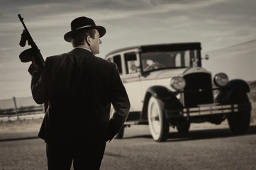 Gangster standing on a road, with a vintage car in the background - fototapety na wymiar