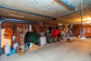 Garage in the basement of the cottage. Shelves with cans, boxes, and tools lined the walls