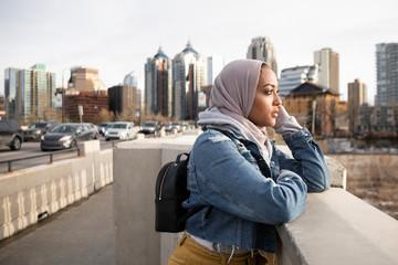 Serene young woman in hijab on urban bridge