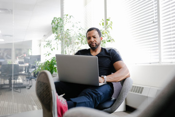 Creative businessman using laptop with feet up in office