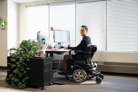 Portrait confident businessman in motorized wheelchair working at offi