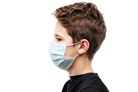 Teenager boy wearing respiratory protective medical mask side view