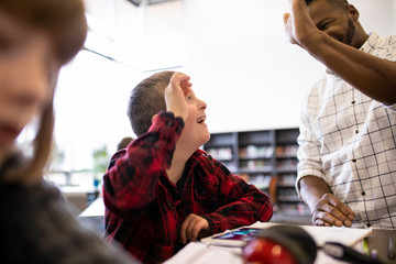Junior high teacher and student with Down Syndrome high fiving in libr