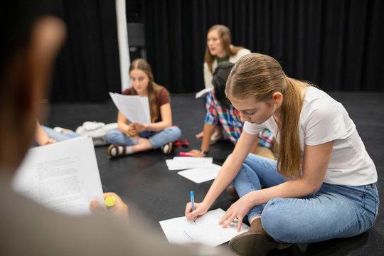 Focused junior high girl student reviewing script in drama class