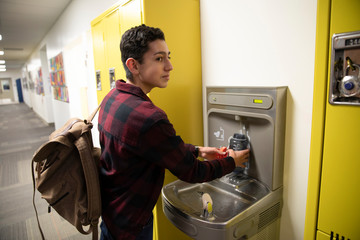 Junior high boy student filling water bottle at corridor water fountai