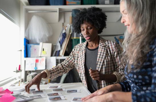 Female costume designers looking at dancer photos in studio