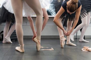 Elegant female ballerinas putting on ballet shoes backstage