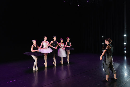 Choreographer and young female ballerinas on stage