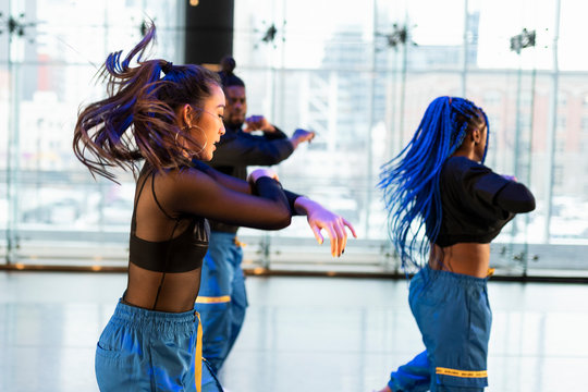 Young female hip-hop dancer rehearsing in studio