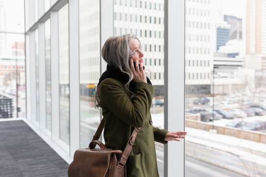 Mature businesswoman talking on smart phone at urban office window