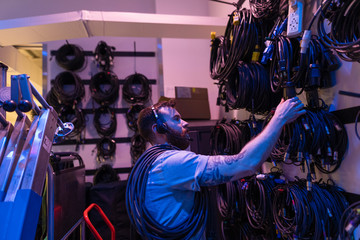 Male stage manager organizing equipment