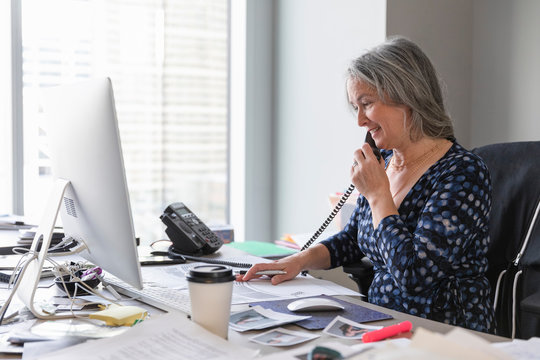 Female theater manager talking on telephone in office