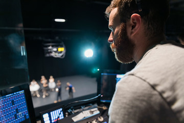Male stage manager operating stage controls above stage