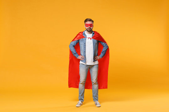 Bearded young man in casual denim clothes, Super hero costume posing isolated on yellow orange background studio portrait. Love family parenthood childhood concept. Standing with arms akimbo on waist.