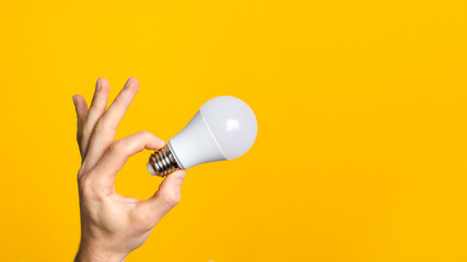 closeup man hand holding white led light bulb against yellow background. concept of ideal, environment ecology and energy efficiency