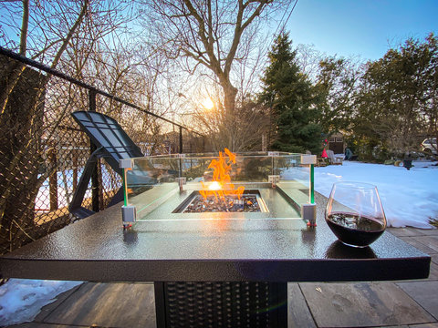 Bronze metal fire table with flames and wine glass nearby