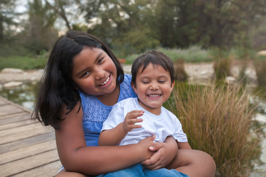 Latino young brother and sister with big smiles and sitting together near a pond, while the older sister is holding the little brother on her lap.