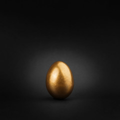 Golden painted egg on black background