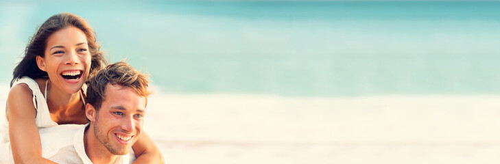 Happy couple in love having fun laughing on summer beach travel vacation panoramic header background. Young lovers on honeymoon, Asian woman, Caucasian man.