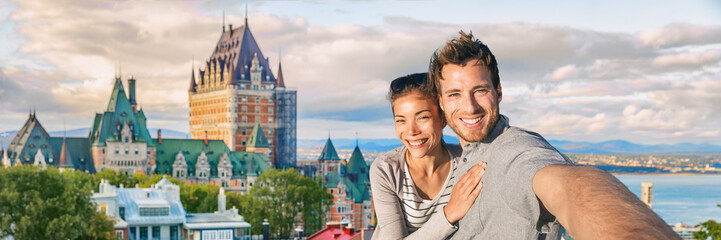 Canada summer travel tourists couple taking selfie photo at famous Quebec city landmark panoramic banner landscape. Happy young people at Frontenac Chateau, Old Quebec. Wall mural