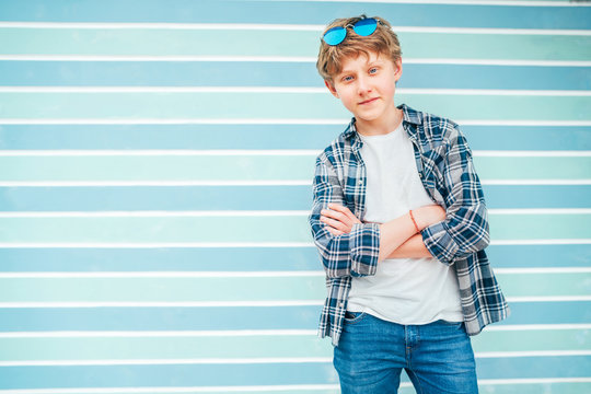 Fashion portrait of caucasian blue-eyed blonde hair 12 year old teenager boy dressed t-shirt and checkered shirt with sunglasses posing on turquoise blue background wall background. Teens fashion.