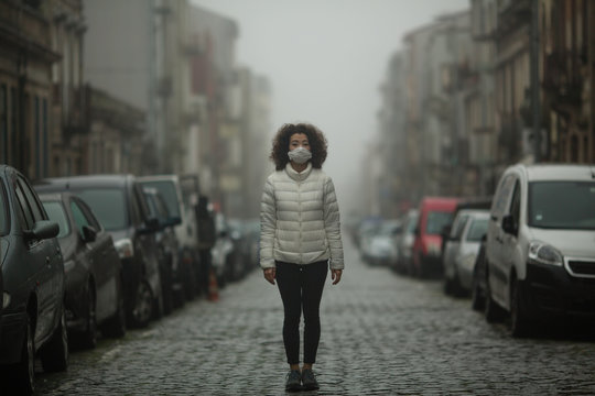 Asian woman in antiviral mask stands in the middle of a deserted street in foggy.