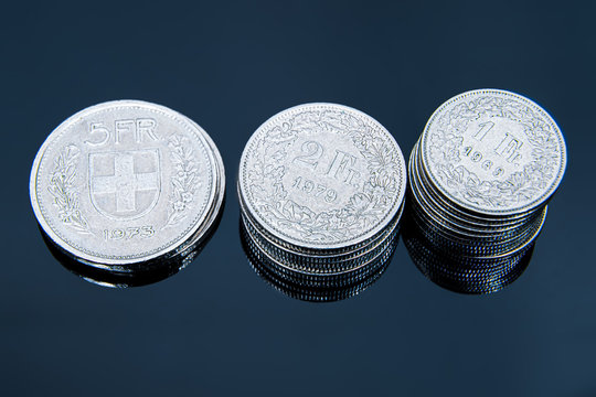 Multiple 1/2, 1, 2, 5 swiss coins franc, centimes CHF money isolated on dark background.