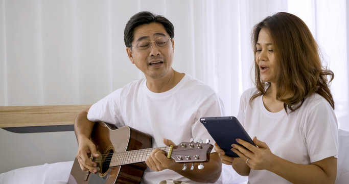 Happy asian lover playing guitar and singing songs together in a room.
