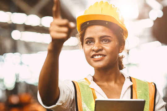 American lady worker in factory maintenance engineer happy working wearing safety uniform and helmet hand pointing and smiling for future of worker welfare concept.