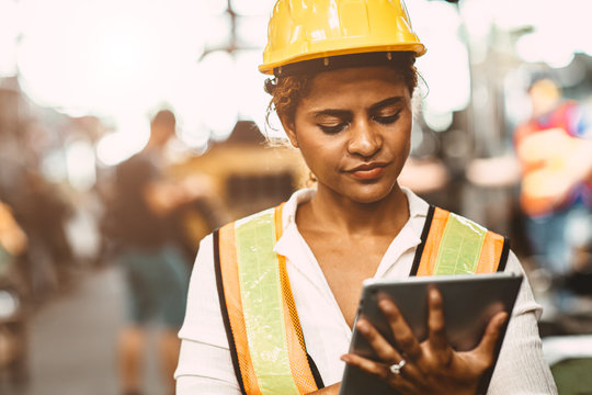 American women worker in heavy Industry maintenance engineer happy working wearing safety uniform and helmet using tablet computer to checking machine in factory.