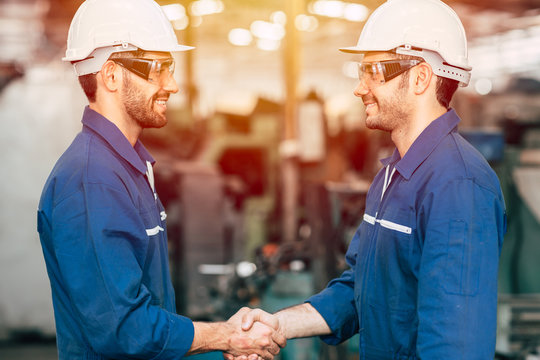 Worker engineer team smiling handshake for finish working dealing job done in factory industry background.
