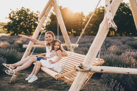 Lovely caucasian mother and her small daughter sitting in a swing with a lavender field on background