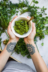Green basil pesto paste dip sauce  in bowl with seeds, nuts and green herbs. Hands hold pesto.
