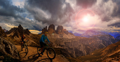 Fotorollo Schokobraun Cycling outdoor adventure in Dolomites. Cycling woman and man on electric mountain bikes in Dolomites landscape. Couple cycling MTB enduro trail track. Outdoor sport activity.