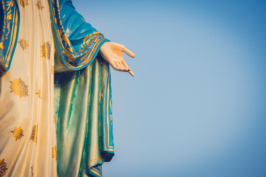 The blessed Virgin Mary statue figure. Catholic praying for our lady - The Virgin Mary. Blue sky copy space on background. Hand closed-up