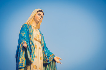 Close-up of the blessed Virgin Mary statue figure. Catholic praying for our lady - The Virgin Mary. Blue sky copy space on background.