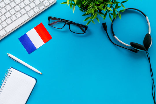 Learn French online. Concept with flag, headset and keyboard on blue background top-down copy space
