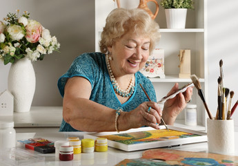 Adult senior woman paints a picture in her studio