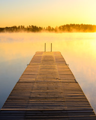 Wooden dock on a misty lake at sunrise