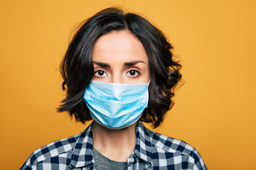 Young serious woman in a protective medical mask. Woman wearing face mask because of Air pollution or virus epidemic.