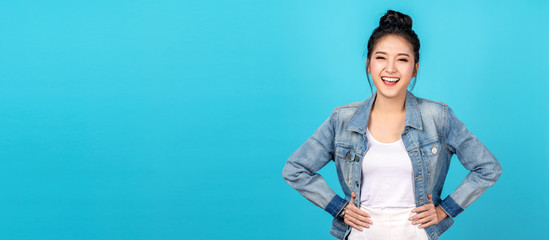 Banner of Happy asian woman standing and feeling happiness and confident on blue background. Cute asia girl smiling or laughing wearing casual travel uniform in jeans shirt and keeping hands on hips Fotomurales
