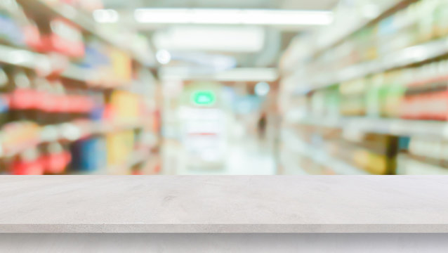 blur local supermarket convenience store background with cement perspective tabletop to showing product or ads banner and promote marketing on display concept