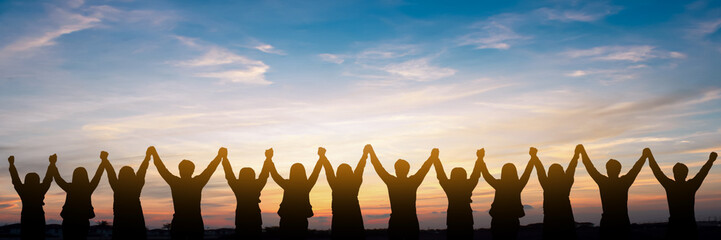 Silhouette of group happy business team making high hands over head in beautiful sunset sky evening time for business success and teamwork concept in company Fototapete