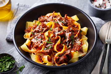 Pasta pappardelle with beef ragout sauce in black bowl. Grey background. Close up.