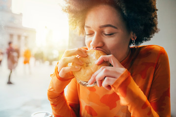 Young beautiful multiethnic woman eating hamburger