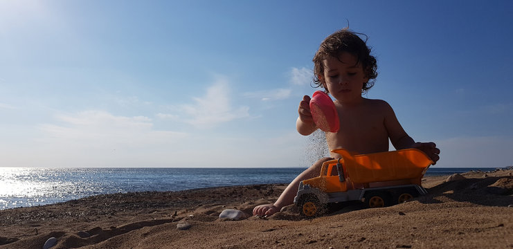 a little boy playing with toy truck on the beach
