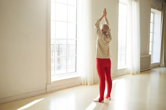 Rear view of fit mature woman with short gray hair doing sun salutation yoga sequence standing barefooted in lit spacious room facing large window, keeping hands together above her head, stretching