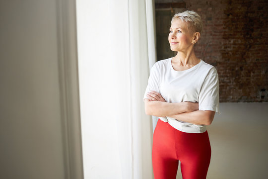 Indoor shot of attractive confident athletic middle aged female wearing white t-shirt and red leggings standing by window keeping arms folded, looking outside and smiling. Mature people and activity